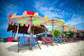 Colorful sun parasols and sundeck chairs on the beach — Stock Photo
