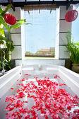 Spa banyosu rahatlamak için gül yaprağı dolu. — Stok fotoğraf