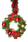 A hanging christmas wreath in green and red with colorful baubles — Foto Stock