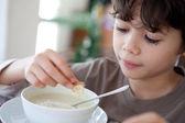 Young boy enjoying a bowl of soup — Stock Photo