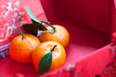 Mini mandarin oranges in a red chinese box — Stock Photo