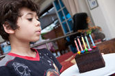 Young boy blowing out candles on a slice of chocolate cake — Stock Photo