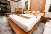 Beautiful kingsize bed in a tropical hotel bedroom. — Stock Photo