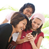 Three young Asian girls sharing a laughter while using a mobile phone — Stock Photo