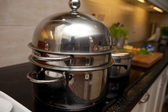Stainless steel pan and pots on stove in the kitchen — Stock Photo