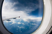 Clouds and sky as seen through window of an aircraft — Stock Photo