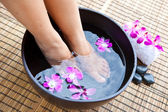 Woman's feet in foot spa bowl with orchids — Stock Photo