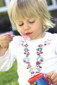 Girl toddler playing with bubbles in the garden — Stock Photo