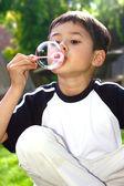 Young boy having fun playing bubbles in the garden — Stock Photo