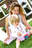 Mother watching her little girl toddler playing with soapy bubbles — Stock Photo