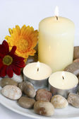 Candles with pebbles and flowers ready for spa setting. — Stock Photo