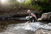 A racer from a participating team makes his way along a river — Stock Photo