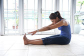 Fitness woman doing her hamstring stretch indoor — Stock Photo