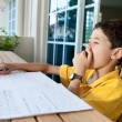 Young boy yawning as he does his homework — Foto de Stock