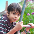 Beautiful young boy on a climbing frame in the garden - Stock Photo