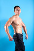 Young fit and muscular Asian man in black denim — Stock Photo