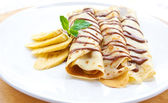 Delicious crepe with banana filling with chocolate sauce — Stock Photo