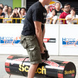 TOA PAYOH, SINGAPORE - MARCH 24 : An male audience tries out the 120kg log used for the log walk in the Strongman Challenge 2012 on March 24, in Toa Payoh Hub, Singapore. — Stock Photo