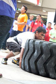 TOA PAYOH, SINGAPORE - MARCH 24 : Contender for Strongman Mohd Asri Abd Kadir attempts the 350kg times 6 flips in the Strongman Challenge 2012 on March 24, in Toa Payoh Hub, Singapore. — Stock Photo