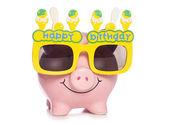 Piggy bank wearing birthday glasses — Stock Photo