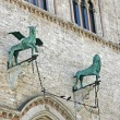 Bronze statues of a winged Griffin and a lion in Perugia - Stock Photo