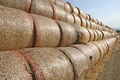 Long row of bales of hay to dry the scorching sun — Stock Photo