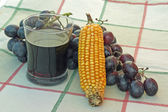 Glass of wine and a bunch of ripe black and yellow corn — Stock Photo