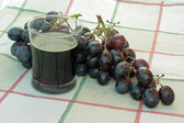 Full glass of wine and a bunch of ripe black grapes — Stock Photo