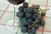 Bunch of black grapes on the autumn tavoglia — Stock Photo