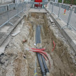 Stock Photo: Road excavation at construction site at conduits for layin