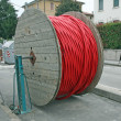 Coils of red high-voltage power cable in the middle of the road - Stock Photo