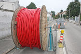 Spool of cable and fiber optics in the road during the outdoor a — Stock Photo