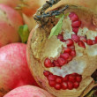Red juicy ripe pomegranate seeds half open - Stock Photo