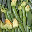 Fresh green zucchini in your parts for sale at vegetable market - Zdjcie stockowe