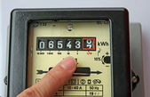 Finger indicating the figures in an electric energy meter — Stock Photo
