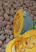 Two half Orange pumpkins on a walnut bed — Stock Photo
