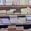 Books stacked on top of each other in a well stocked library — Stockfoto