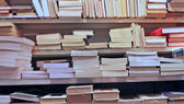 Books stacked on top of each other in a well stocked library — Stok fotoğraf