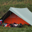 Stock Photo: Orange and green tent with many backpacks