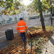 Street Sweeper with orange jacket while blowing the dried leaves — Stock Photo