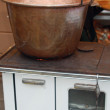 Copper cauldron over an old wood stove — Stock Photo
