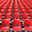 Red chairs of empty stadium but ready to accommodate the fans - Stok fotoğraf