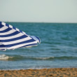 Stock Photo: Striped umbrella on the beach and sea in the background