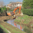 Bulldozer at work on the bed of a river during consolidation of - Stock Photo