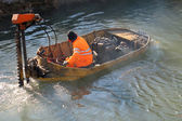 Boat for River Cleanup and a worker — Stock Photo