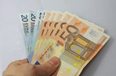 Cash money in euro with the hand of the debtor — Stock Photo