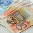 Money and euro banknotes with two wedding rings in gold are on t — Stock Photo