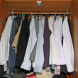 Stock Photo: Inside of closet full of dress shirts and sweaters for men