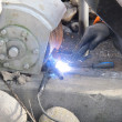 Постер, плакат: While steadfast worker a piece of iron with soldering iron