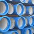Piles of concrete pipes for transporting water and sewerage - Stock Photo